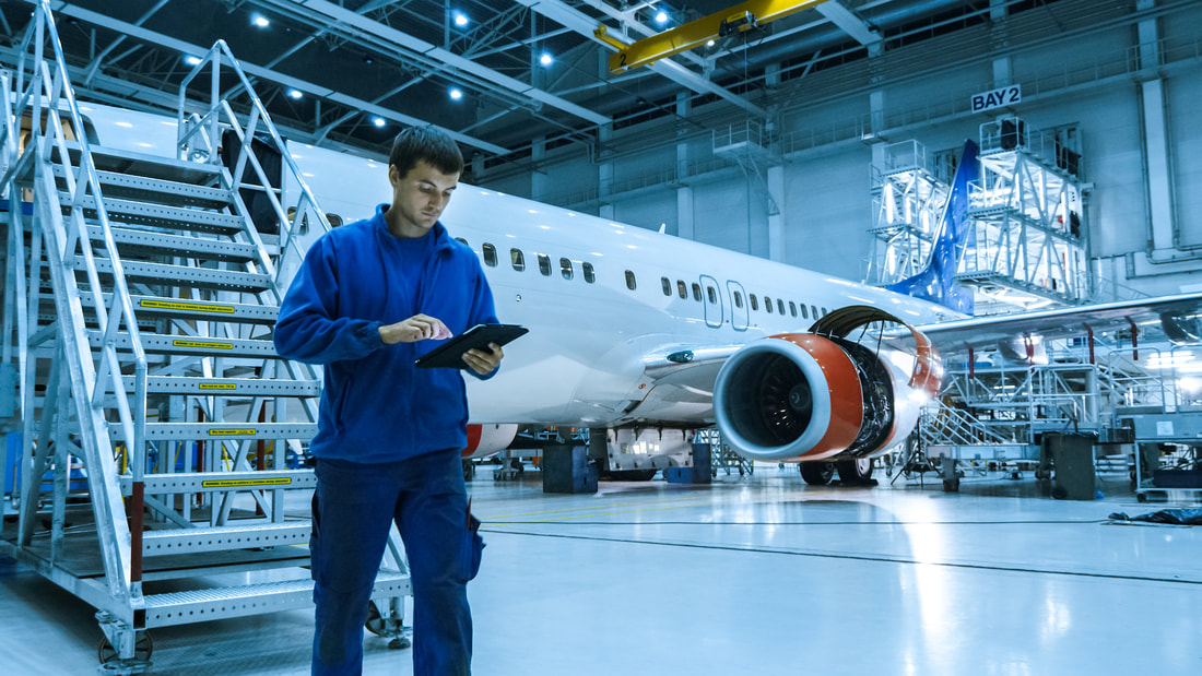 Aircraft maintenance mechanic in blue uniform is going down the stairs while using tablet in a hangar